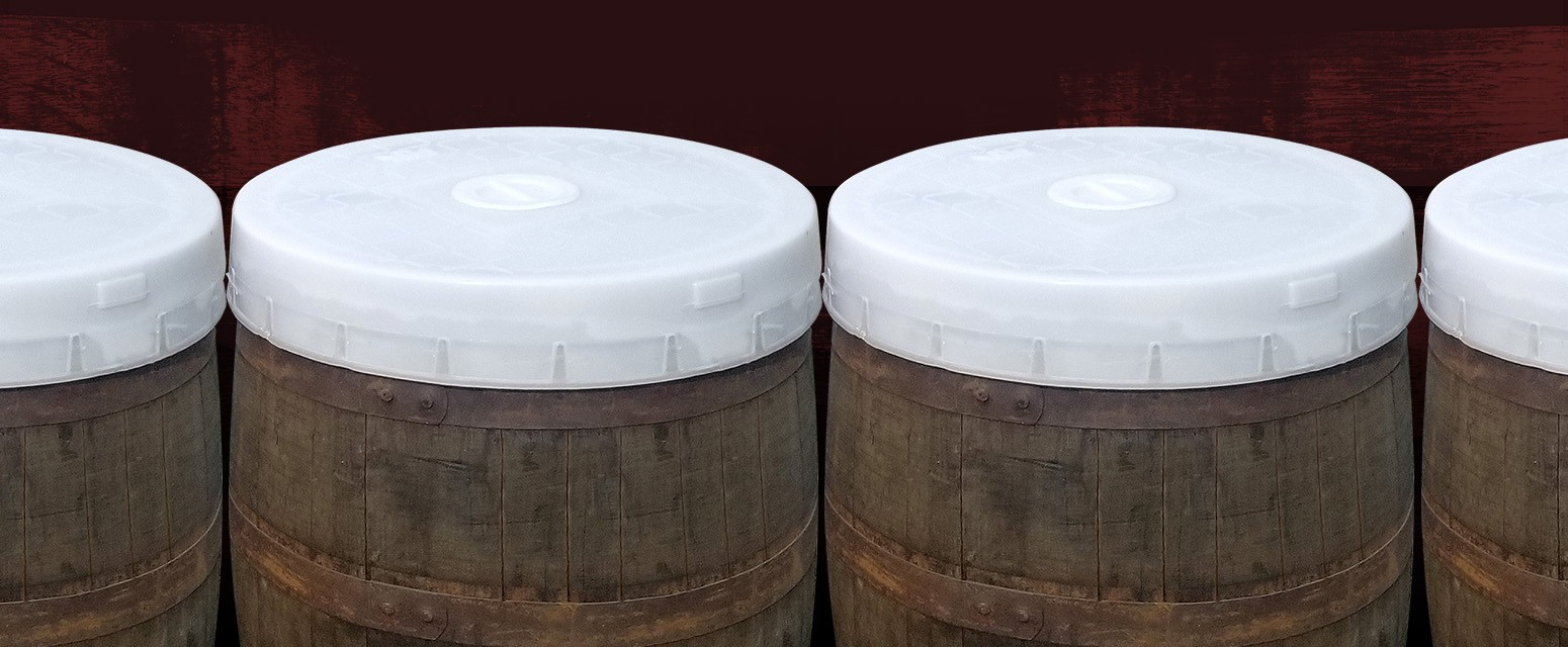 line up of whiskey barrels with spart cap lids